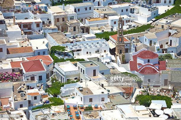 View from the Acropolis of Lindos down to the traditional white cubic houses with roof top restaurants in town on July 04 2010 in Lindos Greece The...