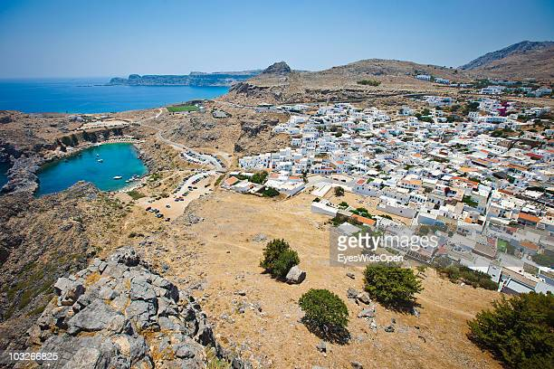 View from the Acropolis of Lindos down to the traditional white cubic houses in town and the most beautiful bay the old harbour Ajios Pavlos on July...