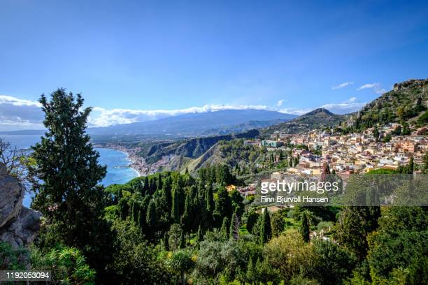 view from the ancient greek theatre in taormina sicily, giardino naxos, the mediterranian and volcano etna in the background - naxos sicily stock pictures, royalty-free photos & images