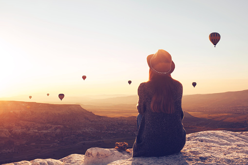 View from the back of a girl in a hat sits on a hill and looks at air balloons. 1057623146