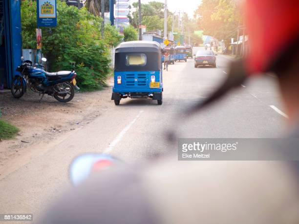 view from the back of a motorcycle Trincomalee aka Gokanna lined with tuk tuks