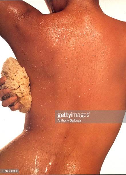 View from the back of an unidentified woman as she scrubs under her raised arm with a loofah sponge New York 1990s