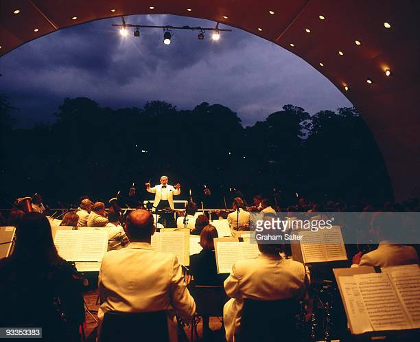 A view from the back of the stage at the Kenwood House Concert Bowl during a classical concert showing the orchestra sheet music and the conductor...