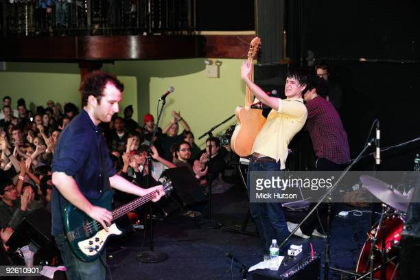 A view from the back of the stage showing Chris Baio and Ezra Koenig of Vampire Weekend performing in front of a cheering audience at The Bowery...