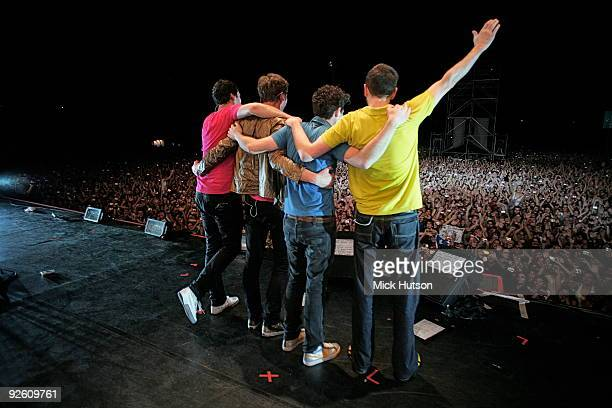 A view from the back of the stage showing Tim RiceOxley Tom Chaplin Jesse Quin and Richard Hughes of Keane posing with their arms around each other...
