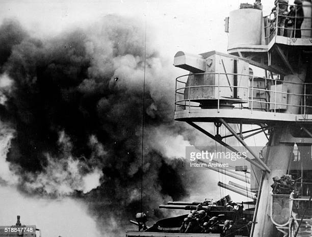 View from the deck of the American battleship USS New York as it fires its main guns off the coast of Iwo Jima February 1945