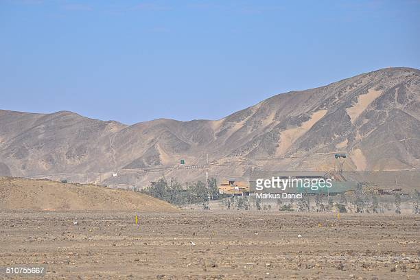 View from the distance of a precious metals mining operation with its buildings and train transportation tracks in the desert and andes mountains in...
