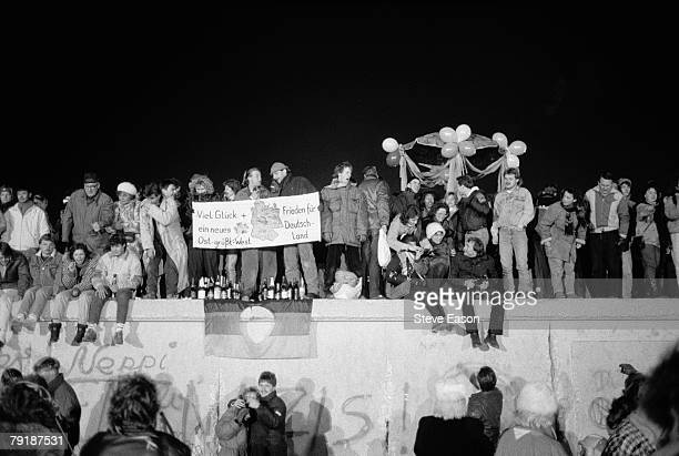 View from the east of Berliners gathered on the Berlin Wall to celebrate the New Year and the effective end of the city's partition, 31st December...