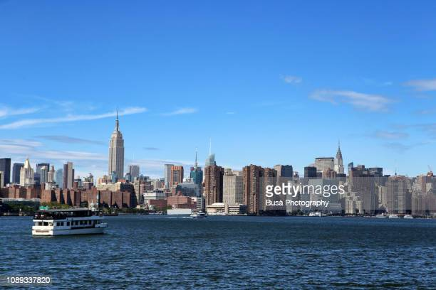 view from the east river of the waterfront of midtown manhattan on a clear sunny day. new york city, usa - east stock pictures, royalty-free photos & images