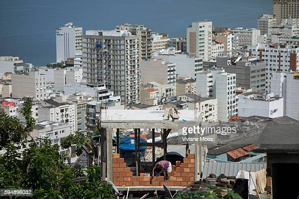 View from the Favela Cantagalo of the contrast between rich and poor building an additional room on top of the home in the traditional way of the...