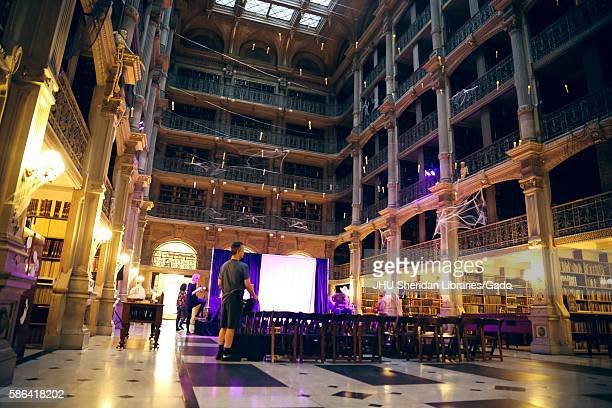 View from the floor to the ceiling of the Peabody Library at the Johns Hopkins University chairs are being lined up in rows in front of the stage on...