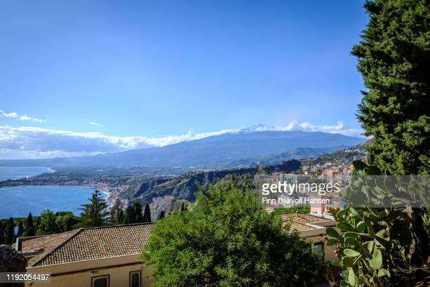 view from the greek theater in taormina, giardino naxos and the vulcano etna in the background - finn bjurvoll stock pictures, royalty-free photos & images
