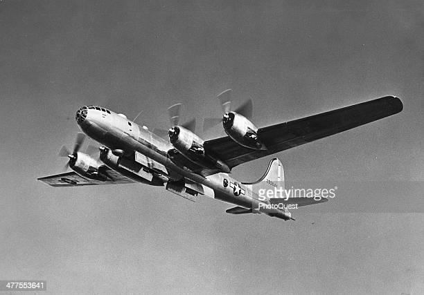 View from the ground as a B29 Superfortress bomber with its bomb bay doors open flies overhead early to mid 1940s
