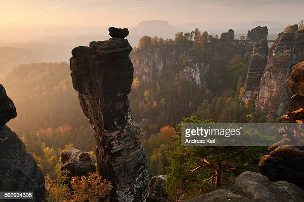 View from the Hoellenhundaussicht view over the Wehlgrund valley to the Bastei rock formation and Basteibruecke bridge, dawn, sunrise, autumn, Saxon Switzerland, Saxony, Germany, Europe