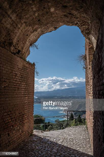 view from the inside of the ancient greek theatre in taormina - giradino naxos and the mediterranian in the background - finn bjurvoll stockfoto's en -beelden