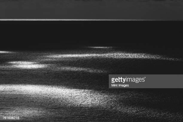 View from the land over the ocean, to the horizon in low light. Sunlight patches on the water surface.