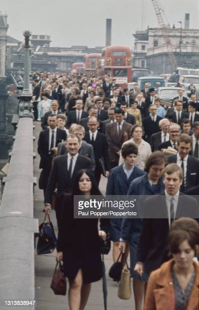 View from the north bank of the River Thames of buses, cars, pedestrians and commuters crossing London Bridge during rush hour in London circa 1965....