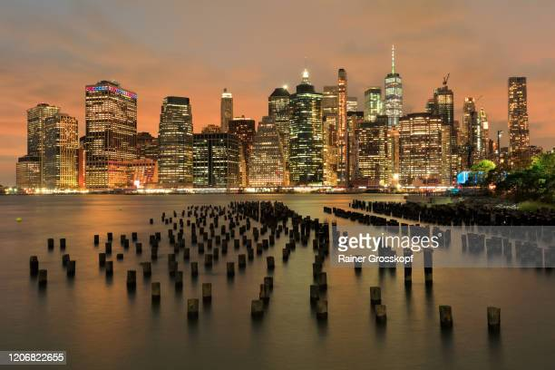 view from the old pier 1 in brooklyn at the illuminated skyline of downtown manhattan at dusk - rainer grosskopf stock pictures, royalty-free photos & images