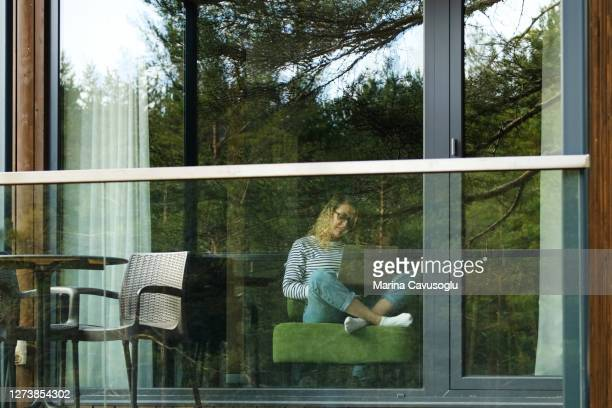 view from the outside on woman working remotely with her laptop and her little child sitting on her knees. - mid adult stock pictures, royalty-free photos & images