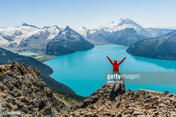 view from the panorama ridge hiking trail, hiker on a rock stretches arms into the air, garibaldi lake, guard mountain and deception peak, back glacier, garibaldi provincial park, british columbia, canada - garibaldi park stock pictures, royalty-free photos & images