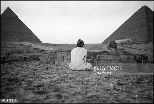 View from the rear of an unidentified man as he sits facing the Great Sphinx and pyramids of Giza at dusk Giza pyramid complex Egypt December 1979