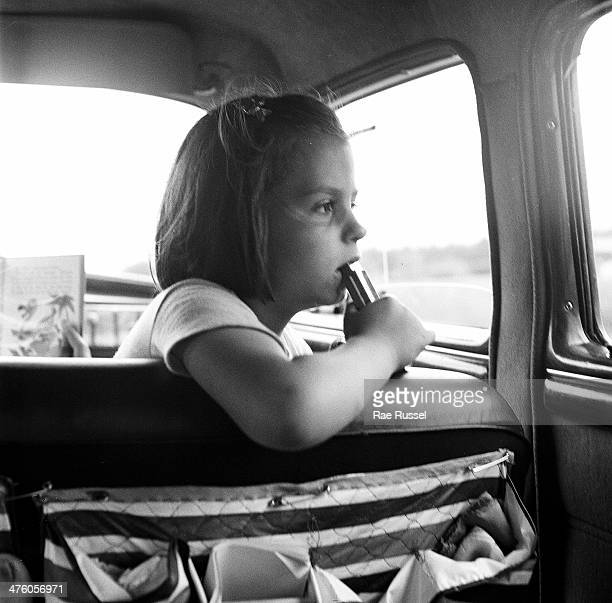View from the rear passenger seat of a girl with a harmonica in her hand as she looks out the window of a car Charlottesville Virginia 1949