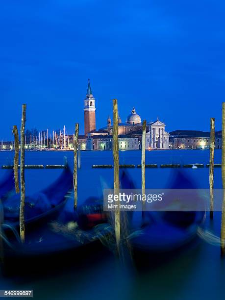 A view from the Riva degli Schiavoni and the Piazza San Marco across the water to the island and church of San Giorgio Maggiore. Gondolas moored at dusk.