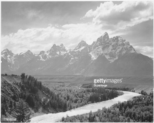 View from the river valley towards snow covered mountains with a river in the foreground Grand Teton National Park Wyoming 1942