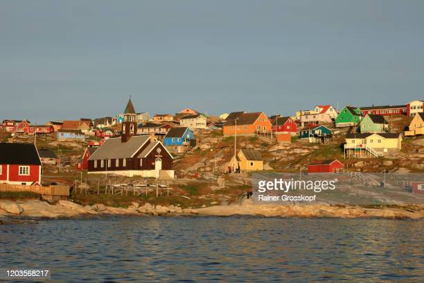 view from the sea at a small town with colorful wooden houses in the warm light of the midnight sun - rainer grosskopf stock pictures, royalty-free photos & images