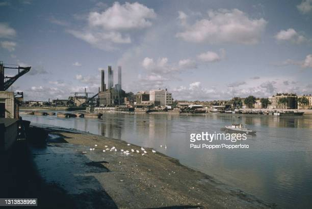 View from the south bank of the River Thames looking westwards and upstream from Battersea Bridge of boats moored at low tide on the north bank of...