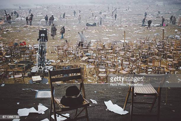 View from the stage as audience members walk amongst discarded rubbish and look towards the empty stage at the end of the Isle of Wight Festival 1970...