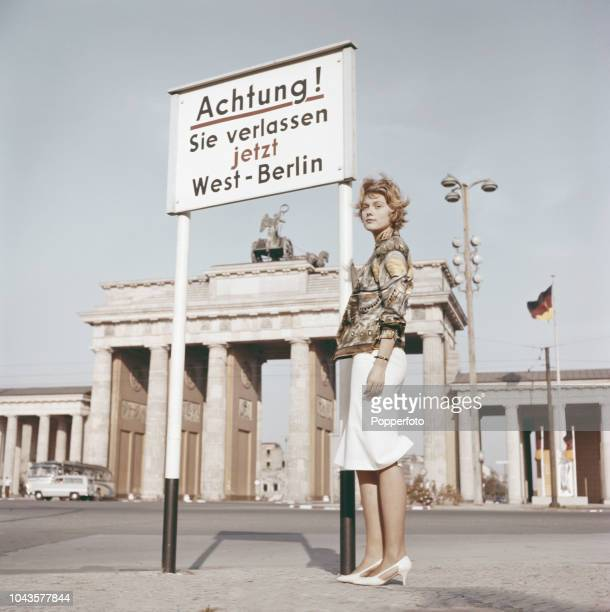 View from the Tiergarten of a young woman standing beside a warning sign in front of the Brandenburg Gate at the border between the British Sector of...