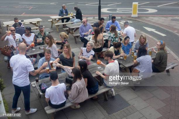 View from the top deck of a London bus of outdoor drinkers siting on benches and raising theor glasses for a toast outside a bar near Oval in south...