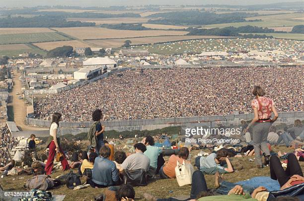 View from the top of Afton Down hill as hippies and members of the audience are pictured sitting on the grass as they look down on events behind the...