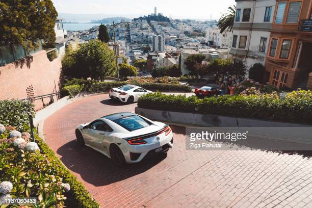 view from the top of lombard street, luxury cars driving down the curvy street - lombard street san francisco stock pictures, royalty-free photos & images