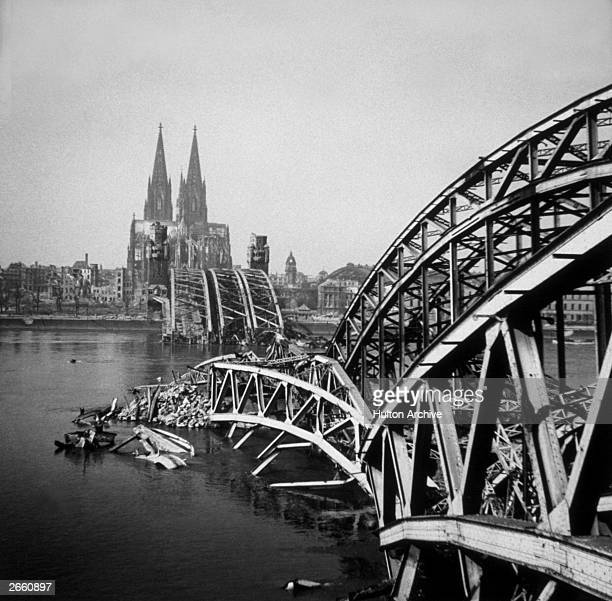 A view from the west side of the River Rhine showing a bomb damaged Hohenzollern Bridge and Cologne Cathedral in the distance