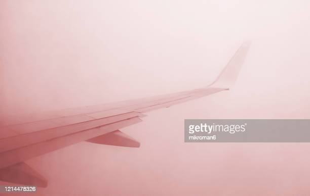 view from the window of an airplane flying in the clouds - 乗り物に乗って ストックフォトと画像