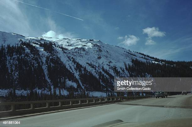 View from the windshield of a car driving on a road through the mountains other cars passing sunny day hills covered in snow and evergreen trees in...
