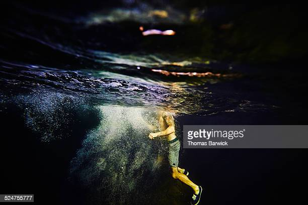 View from underwater of man swimming in river