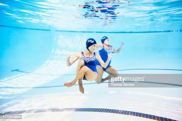 View from underwater of senior female synchronized swimmers underwater during routine