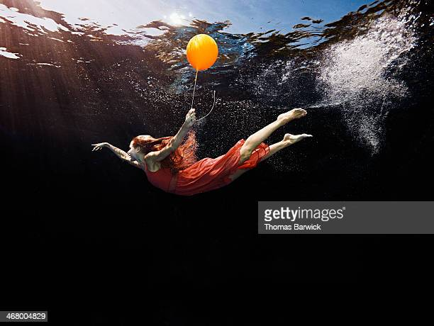 view from underwater of woman holding balloon - traumhaft stock-fotos und bilder