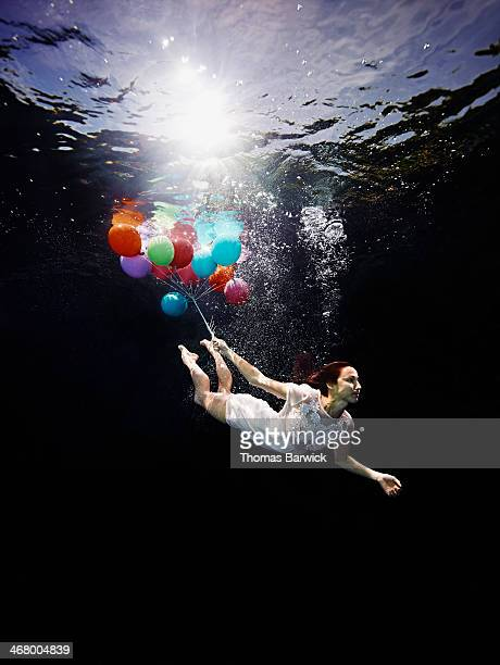 View from underwater of woman holding balloons