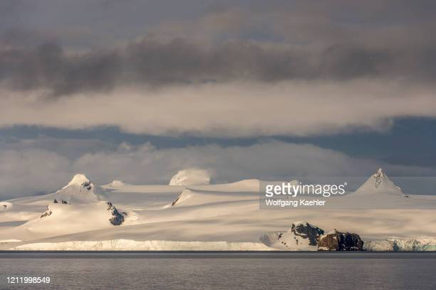 View from Yankee Harbor in the South Shetland Islands off the coast of Antarctica, of Livingston Island emerging out of clouds.