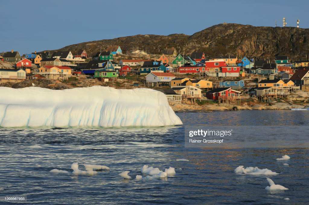 View froom the sea at an iceberg floating in front of colorful wooden houses of a small nordic town : Stock-Foto