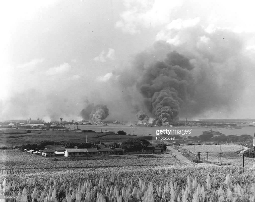 View in the distance of Pearl Harbor smoking from fires caused by the Japanese air raid, December 1941.