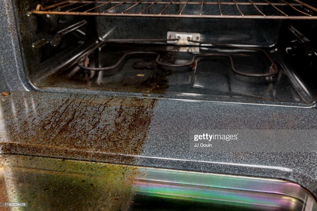 View inside electric oven with one half shiny clean and half filthy covered in burnt grease and food on glass and door. Housecleaning concept and comparison : Stock Photo