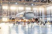 View inside the aviation hangar, the airplane mechanic working around the service.