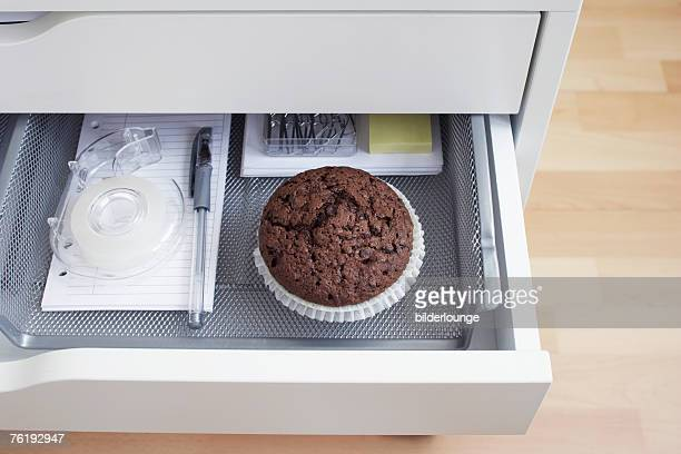 view into open desk drawer containing chocolate muffin