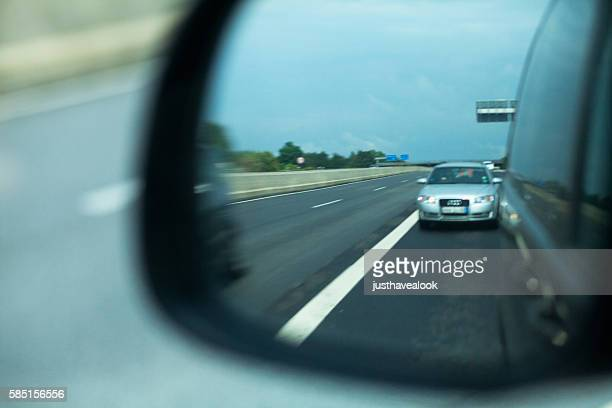 View into side mirror of car on highway