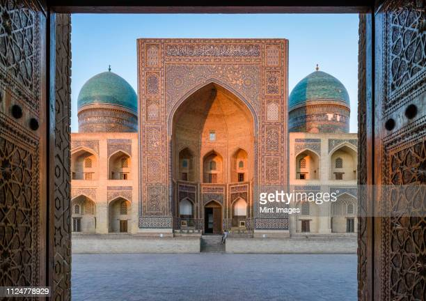 view into the courtyard and the decorated arch and minarets of a madrasa or mosque in bukhara city centre. - uzbekistan foto e immagini stock
